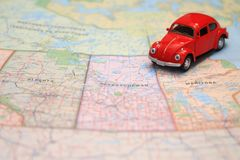 Miniature red car driving on a map of the pairie provinces, canada. Miniature red toy car driving on a map of the pairie provinces, canada stock photo