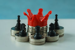 Miniature red crown king on stack of coins and chess symbol as f Stock Photo