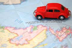 Miniature car driving on a map of Newfoundland Canada. Miniature red toy car driving on a map of Newfoundland Canada royalty free stock images
