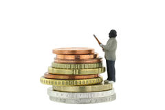 Miniature robber model standing on a pile of Euro coins. Closeup of Miniature robber model standing on a pile of Euro coins, concept for money robbery Stock Photo