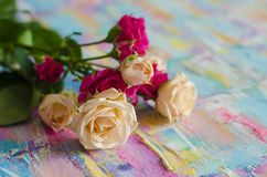 Miniature roses on a beautiful background. Texture of acrylic painting. Festive photocomposition. Stock Photography