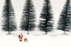 Miniature Santa Claus and artificial Christmas trees with snow background. Stock Photography