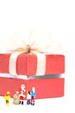 Miniature Santa Claus standing in front of a big gift box. Royalty Free Stock Photography