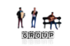 Miniature scale model musicians standing behind the word group. On beads royalty free stock images
