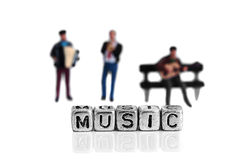 Miniature scale model musicians standing behind the word music stock photo