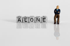 Miniature scale model pensioner with the word alone Royalty Free Stock Images