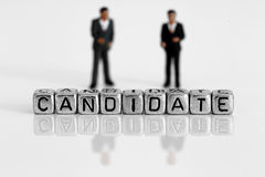 Miniature scale model politicians standing behind the word candidate. On beads royalty free stock photo