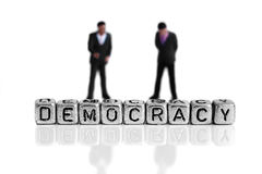 Miniature scale model politicians standing behind the word democracy. On beads royalty free stock photo