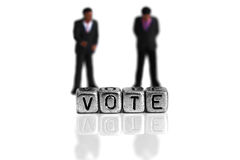 Miniature scale model politicians standing behind the word vote. On beads stock photo