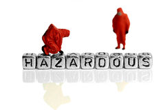 Miniature scale model team in chemical suits with the word hazardous. On beads royalty free stock image