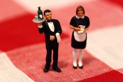 Miniature scale model waiter and waitress on gingham. Miniature scale model waiter and waitress on a gingham tablecloth background Royalty Free Stock Photography