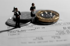Miniature scale model waiter and waitress on a till receipt bill Royalty Free Stock Image