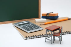 Miniature school desk, chalkboard and calculator on white background. Royalty Free Stock Photos