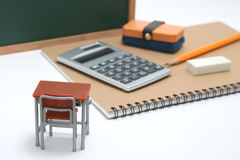 Miniature school desk, chalkboard and calculator on white background. royalty free stock images