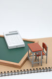 Miniature school desk, chalkboard and calculator on white background. Stock Images