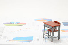 Miniature school study desk and documents with charts and graphs. Stock Photography