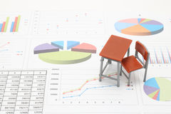 Miniature school study desk and documents with charts and graphs.  Royalty Free Stock Photography