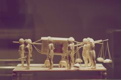 A miniature sculptural composition carved from bone. Servants carry their master royalty free stock images