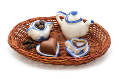 Miniature service for coffee,coffee beans and chocolate hearts in a wicker tray Royalty Free Stock Images