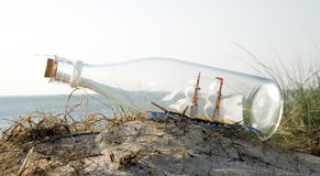 Miniature ship in bottle standing on sand Royalty Free Stock Photo