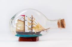 Miniature ship inside a bottle. Handmade miniature ship inside a bottle,  on white background Royalty Free Stock Images