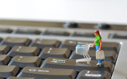 Miniature shopper with shopping cart Royalty Free Stock Photography