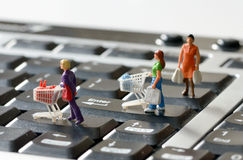 Miniature shoppers  with shopping cart Stock Photos