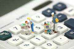 Miniature shoppers standing on a calculator royalty free stock photography