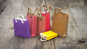 Miniature Shopping Bags. Colorful miniature paper shopping bags on wood background royalty free stock image