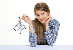 Miniature shopping cart. Young woman with a miniature shopping cart Stock Photography