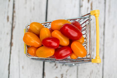 Miniature shopping cart with mini tomatoes Royalty Free Stock Photos