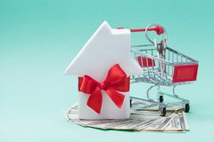 Miniature shopping cart, small white house decorated red bow ribbon, dollars money and keychain. Buying a new home, gift or sale Stock Images