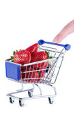 Miniature shopping cart with strawberries and finger Royalty Free Stock Photos