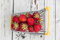 Miniature shopping cart with strawberries Stock Photography
