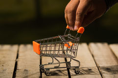 Miniature shopping trolley sitting on wooden surface, big hands touching handle, magicians concept.  Royalty Free Stock Photography
