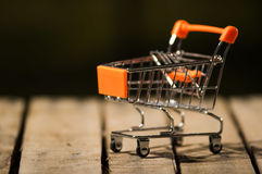 Miniature shopping trolley sitting on wooden surface, magicians concept Stock Image