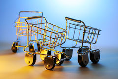 Miniature Shopping Trolleys. On Blue Backgorund Stock Photo