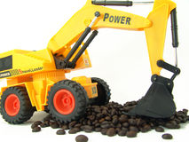 Miniature shovel-loader. Miniature powerful shovel-loader moving coffee beans Royalty Free Stock Image