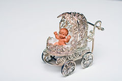 Miniature silver baby buggy containing toy infant Royalty Free Stock Photography