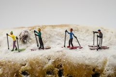 Miniature skier skiing on a cake. Concept Miniature skier skiing on a white cake Royalty Free Stock Images