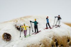 Miniature skier skiing on a cake. Concept Miniature skier skiing on a white cake Stock Images