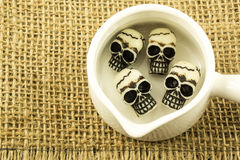 Miniature skull inside white pot, sack background Stock Image