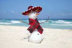 Miniature snowman wearing Mexican sombrero and scarf on the beac. H in Cancun Stock Photos