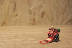 Miniature statue  and red vintage oriental rickshaw cab Royalty Free Stock Photos