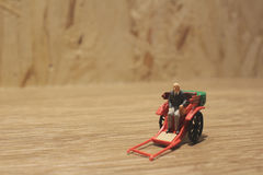 Miniature statue  and red vintage oriental rickshaw cab Stock Image