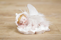 Miniature statue of white angel with wings on wooden surface. Royalty Free Stock Photo