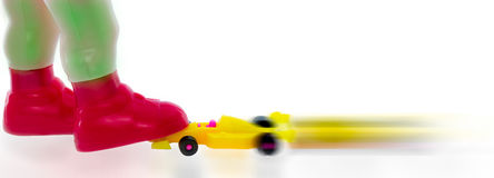 Miniature is stopping a fast moving miniature formula car with its shoe. Royalty Free Stock Photos