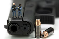 Miniature SWAT team standing on a gun. Royalty Free Stock Photography