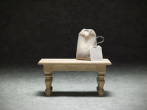 Miniature table with a tea bag. On dark background Royalty Free Stock Photography