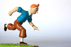 A miniature of Tintin. A painted metallic miniature of Tintin (Herge character), running after Snowy Royalty Free Stock Images